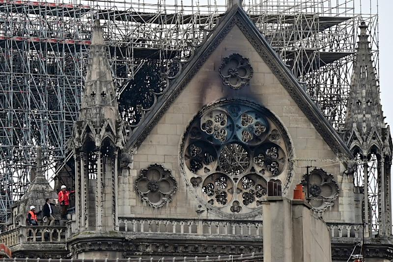 Inspectors inspect the badly damaged roof at Notre-Dame on a day which saw pledges of millions of dollars to restore the iconic site