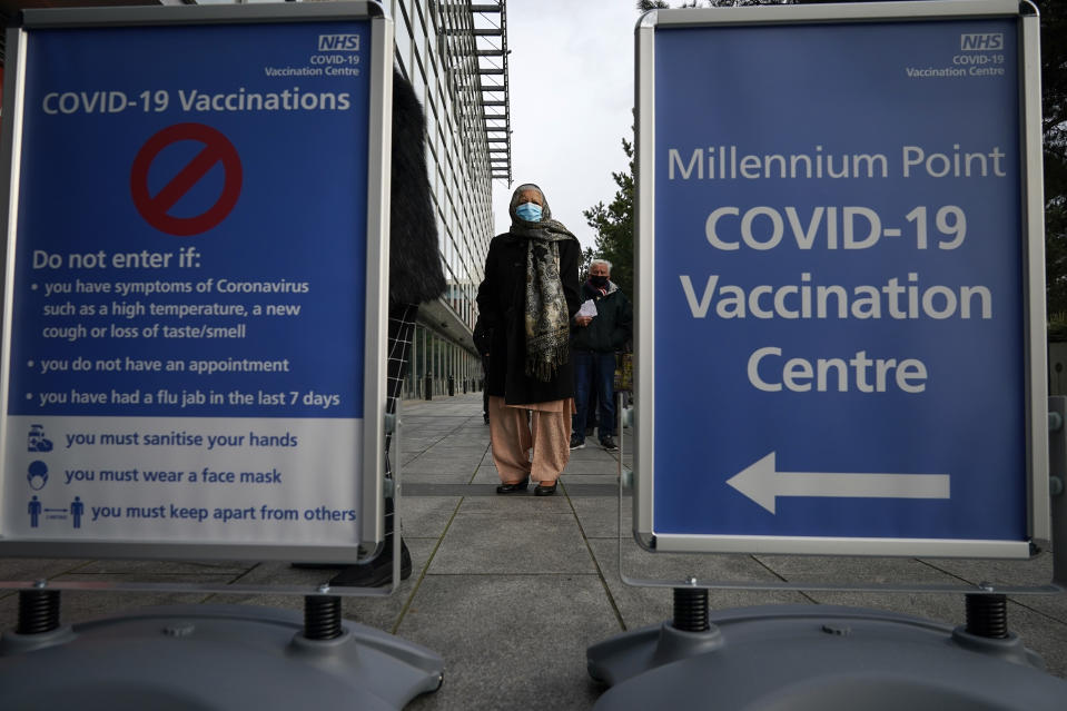 BIRMINGHAM, ENGLAND - JANUARY 11: People queue outside the mass NHS Covid-19 vaccine centre that has been set up at the Millennium Point centre in Birmingham on January 11, 2021 in Birmingham, England. The location is one of several mass vaccination centres in England to open to the public this week. The UK aims to vaccinate 15 million people by mid-February. (Photo by Christopher Furlong/Getty Images)