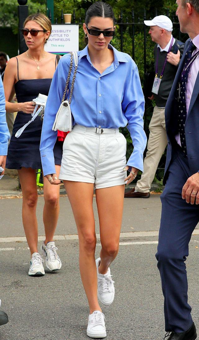 in a preppy blue button-down shirt, white belted short, white sneakers and a white chainlink bag at the Wimbledon Tennis Championships in London.