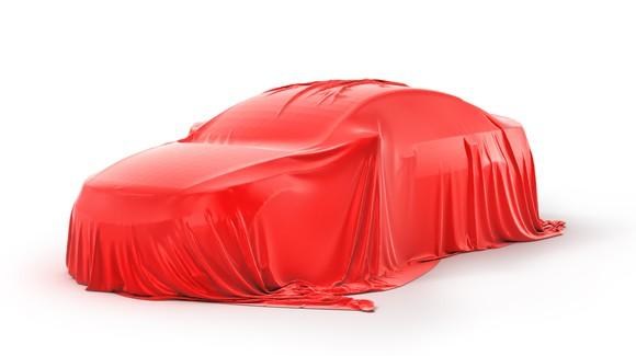 Image of a car with a red sheet on top of it.