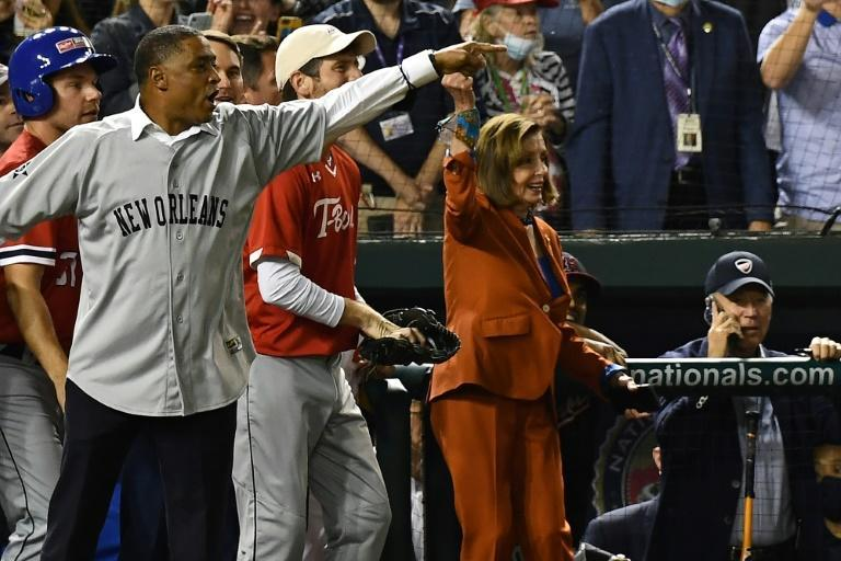 The speaker of the US House of Representatives, Nancy Pelosi (C), cheers as President Joe Biden (R) has a phone conversation from the Democrats' dugout during the Congressional Baseball Game at Nationals Park in Washington (AFP/Brendan Smialowski)