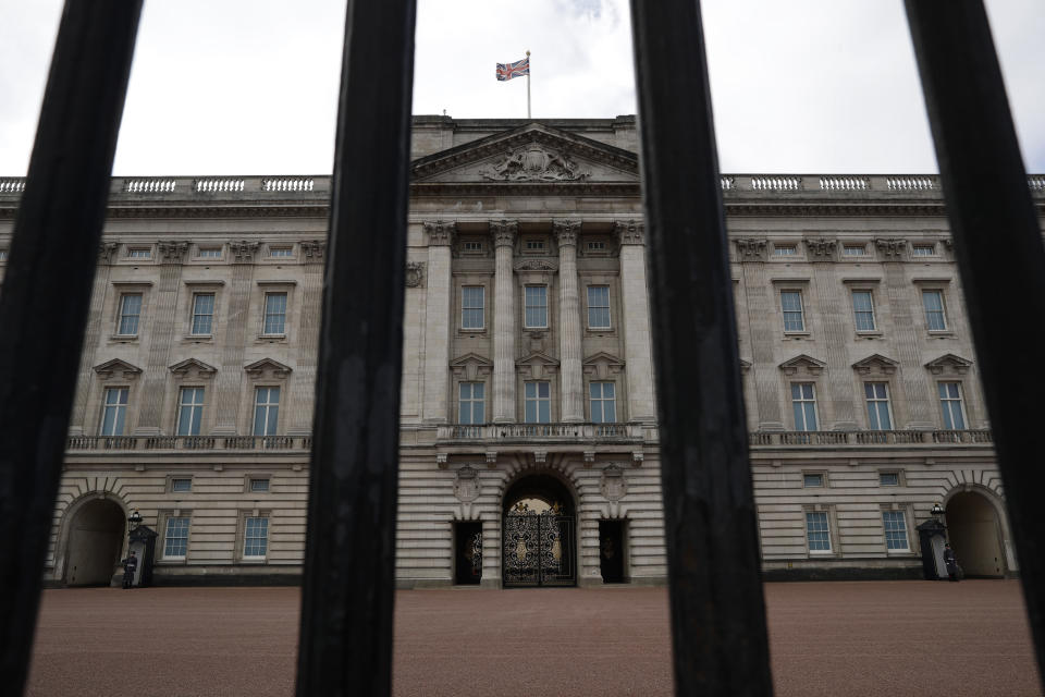 Buckingham Palace, the official London residence of Britain's Queen Elizabeth II is seen through the rails of its fence in central London, Sunday, March 7, 2021. The time has finally come for audiences to hear Meghan and Harry describe the backstory and effects of their tumultuous split from royal life. British audiences will wake up Monday to headlines and social media posts about Oprah Winfrey's 8 p.m. Sunday U.S. Eastern time interview, but won't be able to see the full interview until Monday night when it airs on ITV. (AP Photo/Matt Dunham)