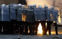 Serbian riot police shields themselves as they clash with protesters in Belgrade, Serbia, Wednesday, July 8, 2020. Serbia's president Aleksandar Vucic backtracked Wednesday on his plans to reinstate a coronavirus lockdown in Belgrade after thousands protested the move and violently clashed with the police in the capital. (AP Photo/Darko Vojinovic)