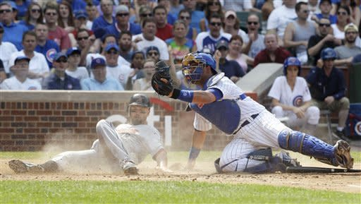 Chicago Cubs catcher Geovany Soto, right, holds up the ball after tagging out Houston Astros' Scott Moore during the third inning of a baseball game in Chicago, Saturday, June 30, 2012. (AP Photo/Nam Y. Huh)