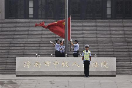 Policemen hoist a Chinese national flag in front of an entrance of the Jinan Intermediate People's Court where the trial of disgraced Chinese politician Bo Xilai will be held, in Jinan, Shandong province September 22, 2013.