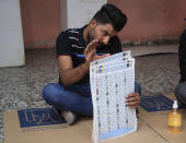 An election worker counts ballots after polls close, at a polling station in Baghdad, Iraq, Sunday, Oct. 10, 2021. Polls have closed across Iraq Sunday evening in parliamentary elections that were held months ahead of schedule in response to a popular uprising against corruption and mismanagement. (AP Photo/Hadi Mizban)