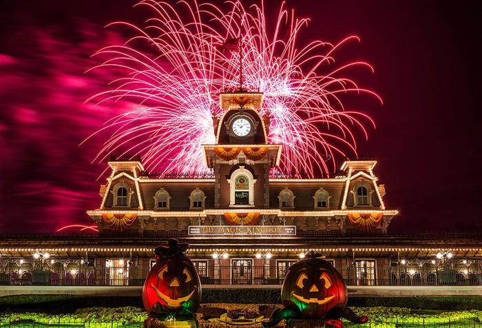 Halloween inspired fireworks at Disney with a pair of jack-o-lanterns in front of the train station.