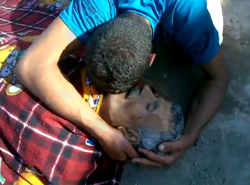 This citizen journalism image made from video provided by Shaam News Network SNN purports to show a man mourning a victim killed by violence that, according to anti-regime activists, was carried out by government forces in Tremseh, Syria, about 15 kilometers (nine miles) northwest of the central city of Hama, Thursday, July 12, 2012. The accounts, some of which claim more than 200 people were killed in the violence Thursday, could not be independently confirmed, but would mark the latest in a string of brutal offensives by Syrian forces attempting to crush the rebellion. (AP Photo/Shaam News Network, SNN) THE ASSOCIATED PRESS IS UNABLE TO INDEPENDENTLY VERIFY THE AUTHENTICITY, CONTENT, LOCATION OR DATE OF THIS IMAGE