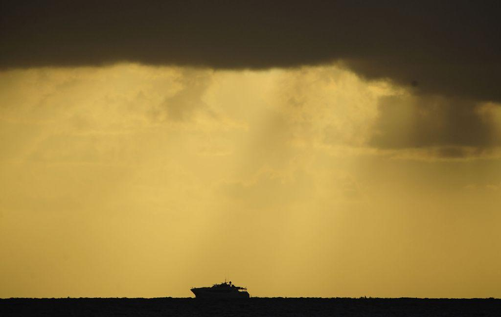 A boat is seen on the horizon just before the start of the total solar eclipse.