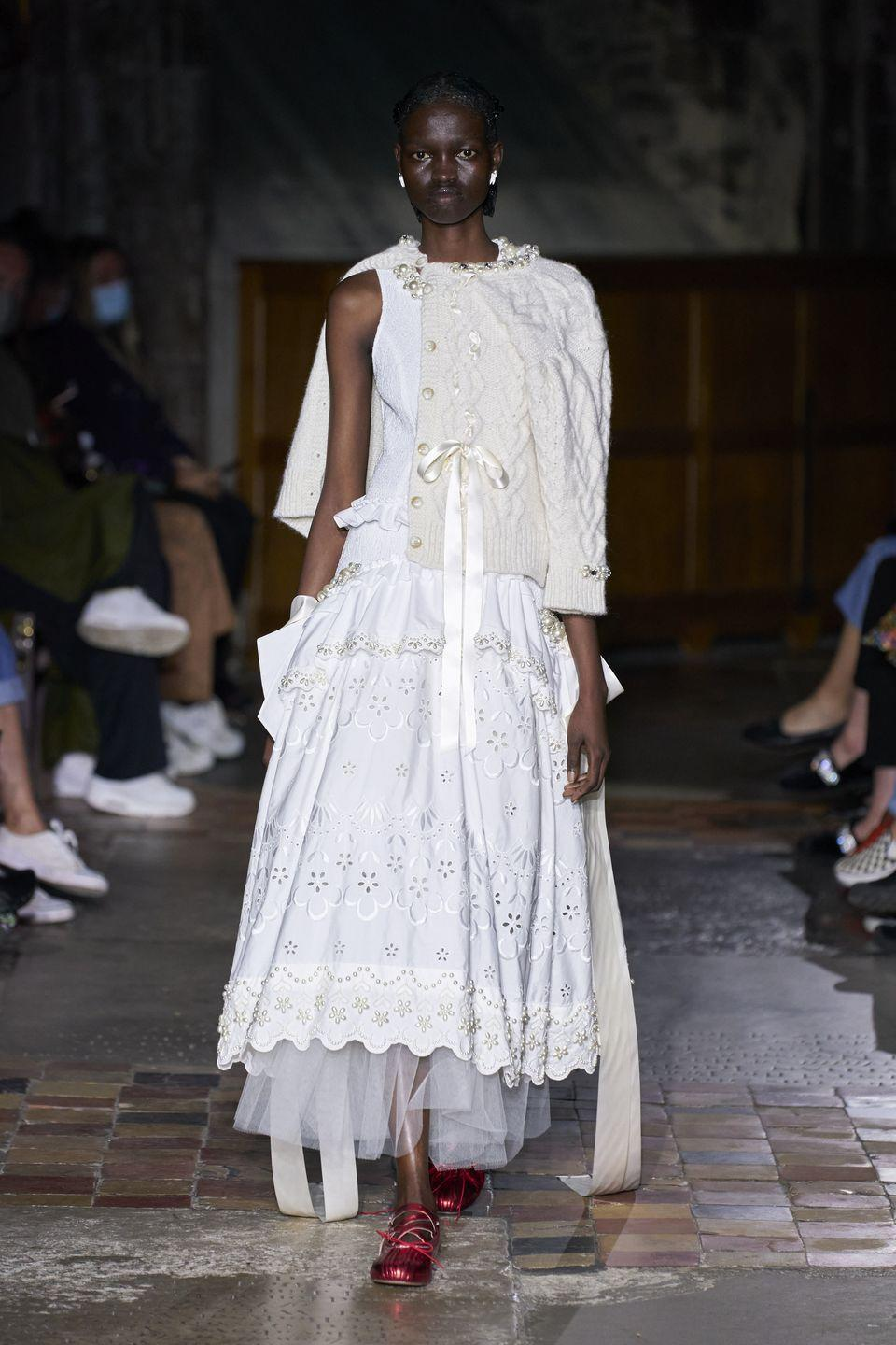 """<p>This season marked Simone Rocha's 10-year anniversary, and the designer chose to focus on the topic of mother-daughter relationships. """"I wanted to blow up those childlike proportions and distort them, mix them with the sleepless nights that come with having a daughter,"""" <a href=""""https://wwd.com/runway/spring-2022/london/simone-rocha/review/"""" rel=""""nofollow noopener"""" target=""""_blank"""" data-ylk=""""slk:she explained"""" class=""""link rapid-noclick-resp"""">she explained</a>, while she also referenced """"the nursing bra, the breast and the nourishing nature of the milk — sharing it and elevating it with these embellished bras.""""</p>"""