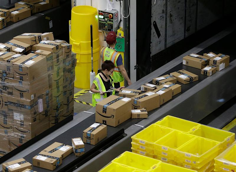 FILE- In this Feb. 9, 2018, file photo, packages move down a conveyor system to the proper shipping area at the new Amazon Fulfillment Center in Sacramento, Calif. The Environmental Protection Agency says it has reached a $1.2 million settlement with Amazon over the sale of illegal pesticides. The pesticides were sold by independent sellers who offered the products through Amazon's website. (AP Photo/Rich Pedroncelli, File)