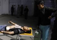 An injured man lies on a stretcher in a hospital after a suicide bombing in Kabul