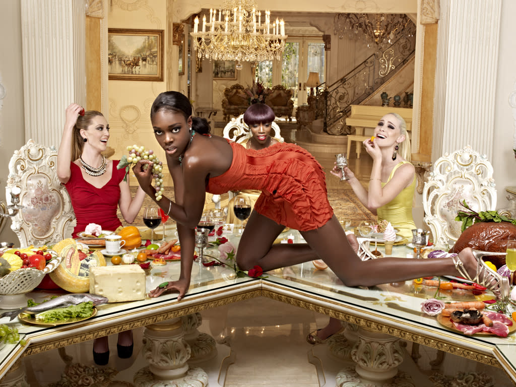 """Kyle, Alisha, and Laura in a photo shoot posing with singer Estelle as art installations during a dinner party on """"America's Next Top Model."""""""