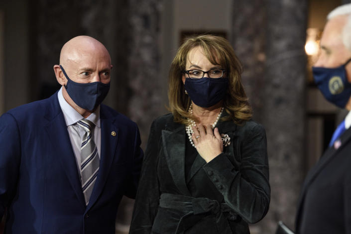 FILE - In this Dec. 2, 2020, file photo, Sen. Mark Kelly, D-Ariz., talks with his wife former Rep. Gabby Giffords, D-Ariz., and Vice President Mike Pence after participating in a re-enactment of his swearing-in on Capitol Hill in Washington. As a mob laid siege to the U.S. Capitol this week, former Rep. Gabby Giffords could only wait nervously for news about her husband, Mark Kelly, who was barely a month into his job as a newly elected senator from Arizona. A decade earlier it was Kelly enduring the excruciating wait for news about Giffords, who was shot in the head in an attempted assassination that, like Wednesday's siege, shocked the nation and prompted a reckoning about the state of politics and discourse in the United States. (Nicholas Kamm/Pool via AP, File)