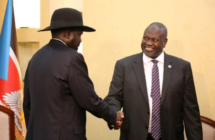 South Sudan's President Salva Kiir Mayardit shakes hands with Riek Machar, ex-vice president and former rebel leader, during their meeting at the State House in Juba