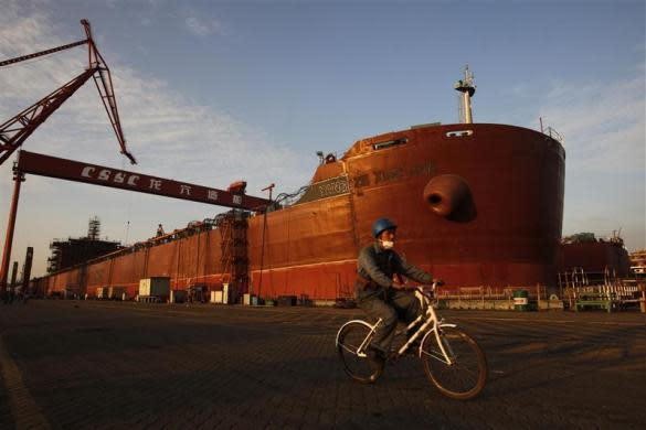 An employee rides a bicycle past a nearly completed ship at China State Shipbuilding Corporation (CSSC) Longxue shipbuilding, in the southern Chinese city of Guangzhou November 13, 2011.