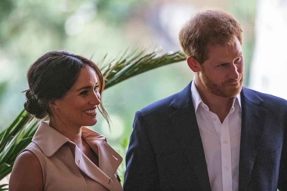 Britain's Prince Harry, Duke of Sussex(R) and Meghan, the Duchess of Sussex(L) stand on the stage at the British High Commissioner residency in Johannesburg where they  will meet with Graca Machel, widow of former South African president Nelson Mandela, in Johannesburg, on October 2, 2019. - Prince Harry recalled the hounding of his late mother Diana to denounce media treatment of his wife Meghan Markle, as the couple launched legal action against a British tabloid for invasion of privacy. (Photo by Michele Spatari / AFP) (Photo by MICHELE SPATARI/AFP via Getty Images)