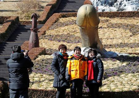 """Tourists pose near a statue in South Korea's Haeshindang Park, also know as """"penis park"""", a shrine to fertility dedicated to the legend of a local girl who died a virgin, in Sinnam, South Korea, February 12, 2018. Picture taken February 12, 2018. REUTERS/Eric Gaillard"""