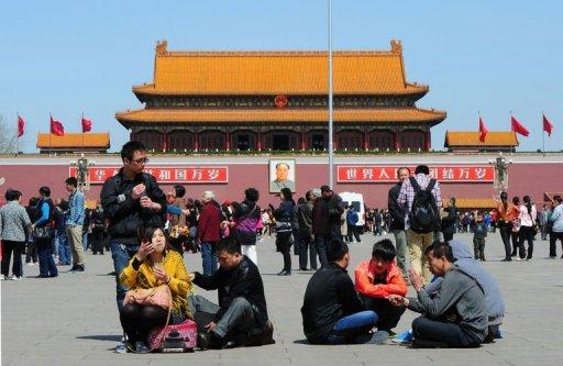 Chinese tourists sit in front of the portrait of the late Chinese leader Mao Zedong in Tiananmen Square in Beijing on April 11, 2012. The spectacular fall from grace of Chinese Communist Party leader Bo Xilai has triggered a riveting political scandal seeped in twists and turns worthy of a Hollywood thriller or detective novel