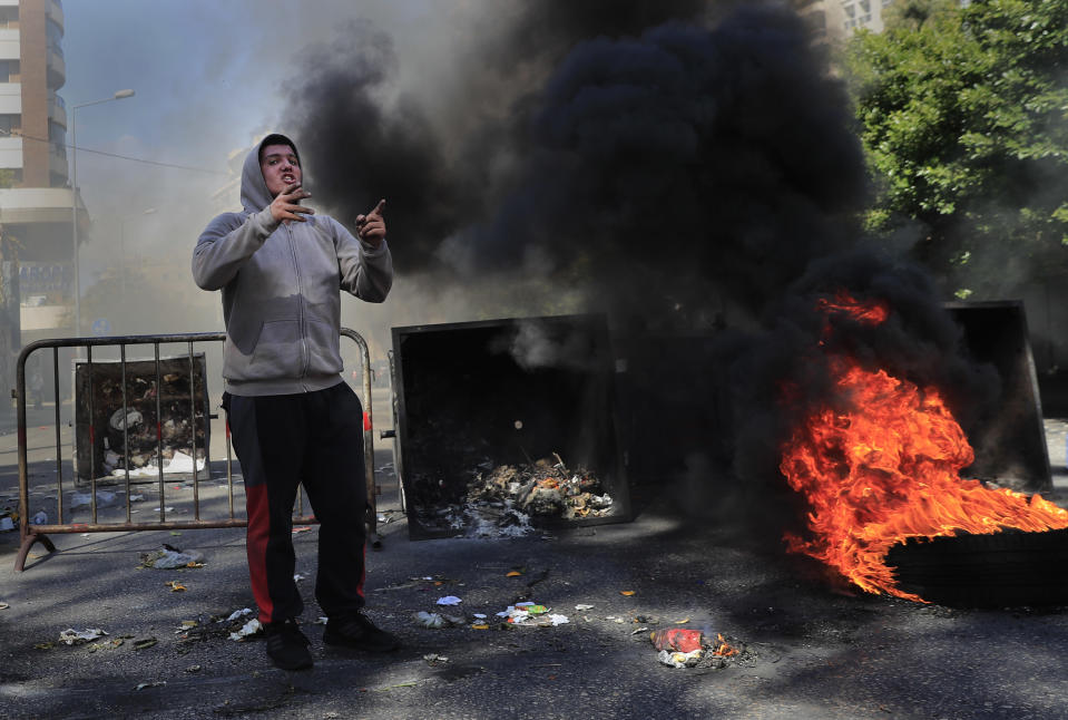 A protester shouts slogans in front of burning tires and garbage containers set on fire to block a main road during a protest against the increase in prices of consumer goods and the crash of the local currency, in Beirut, Lebanon, Tuesday, March 16, 2021. Scattered protests broke out on Tuesday in different parts of the country after the Lebanese pound hit a new record low against the dollar on the black market. (AP Photo/Hussein Malla)