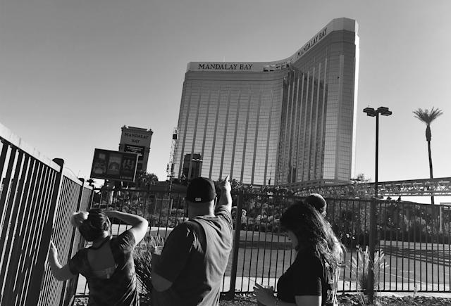 A man points to broken out windows at the Mandalay Bay Resort and Casino Monday where police say accused shooter Stephen Paddock took deadly aim at concertgoers. (Photo: Holly Bailey/Yahoo News)