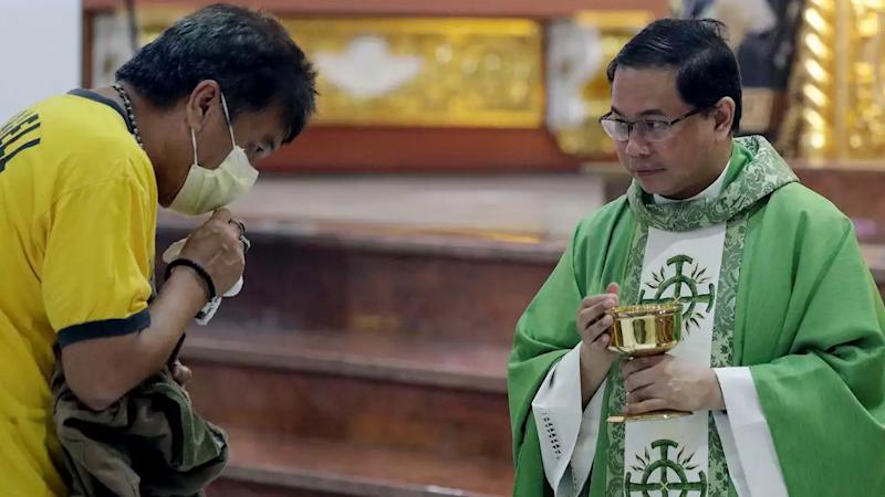 Catholic priest Fr. Joseph Arellano, right, looks at a man who forgot to take off his protective mask and tried to insert the host in his mouth during communion at a mass at the Minor Basilica of San Lorenzo Ruiz in Manila's Chinatown, Philippines. Image credit: AP