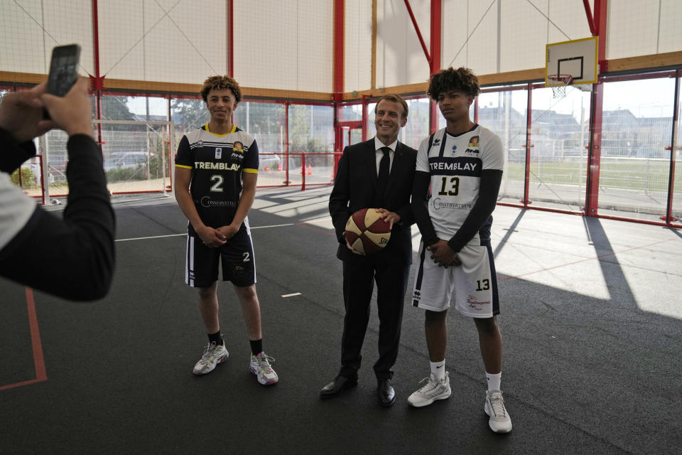 French President Emmanuel Macron poses with youths at a basketball playground in Tremblay-en-France, outside Paris, Thursday, Oct.14, 2021. French President Emmanuel Macron will promote sports ahead of the 2024 Olympic Games in Paris. (AP Photo/Francois Mori, Pool)