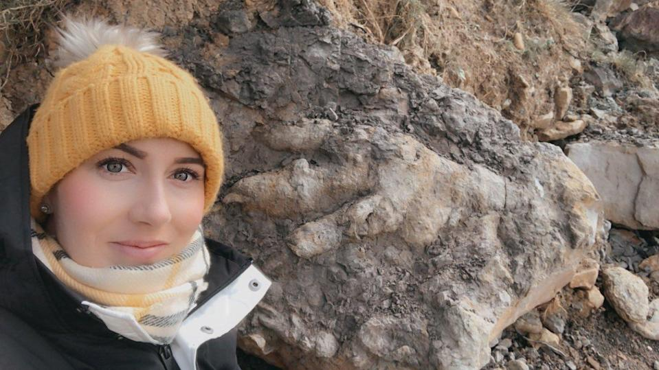 Marie Woods with the giant dinosaur footprint she found on a Yorkshire beach (Marie Woods/PA)