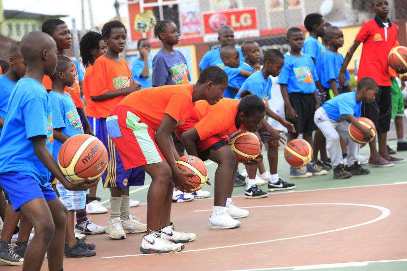 """In this photo taken Tuesday, Sept . 10, 2013, children learn passes and basic moves during a basket ball camp organized by former Seattle Supersonics and Orlando Magic center Olumide Oyedeji, in Lagos, Nigeria. About 30 years after NBA Hall of Famer Hakeem """"The Dream"""" Olajuwon first emerged from the sprawling city of Lagos, basketball is gaining momentum in this West African country of nearly 160 million people which, like most of the continent, has had little space for any sport other than soccer. (AP Photo/Sunday Alamba)"""