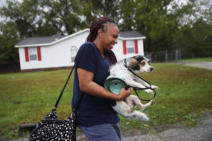 FAYETTEVILLE, NC - SEPTEMBER 16: Dominique Capers carries her dog Lougie as she evacuates her home ahead of possible flood waters after Hurricane Florence passed through the area on September 16, 2018 in Fayetteville, North Carolina.