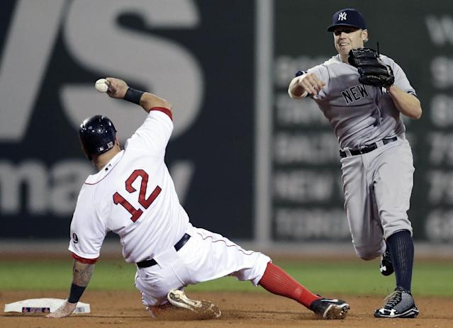 Boston Red Sox first baseman Mike Napoli (12) slides out on a fielder's choice as New York Yankees' Brendan Ryan, right, tries to throw to first base in the fourth inning of a baseball game at Fenway Park, in Boston, Sunday, Sept. 15, 2013. (AP Photo/Steven Senne)