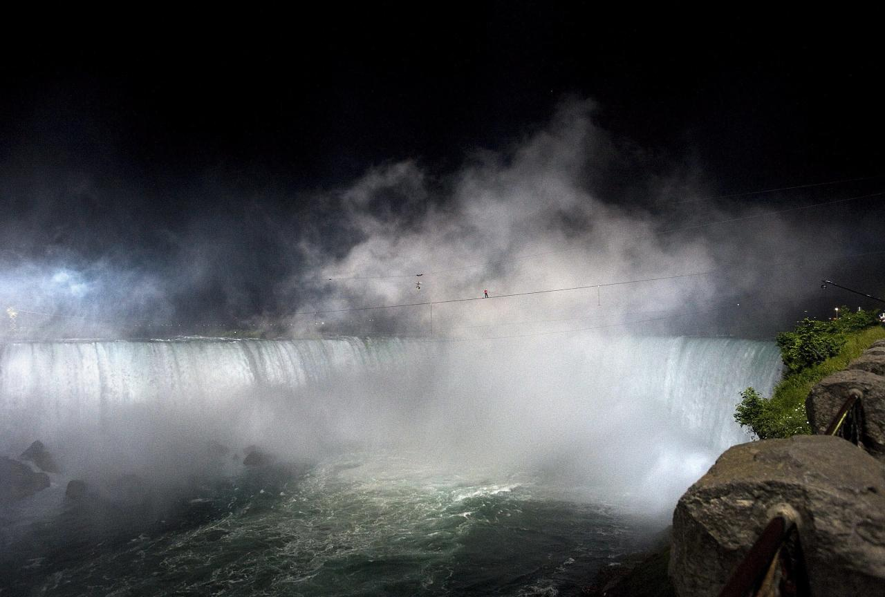 Nik Wallenda nears the middle of his tightrope walk over Niagara Falls as seen from Niagara Falls, Ontario, on Friday, June 15, 2012. Wallenda has finished his attempt to become the first person to walk on a tightrope 1,800 feet across the mist-fogged brink of roaring Niagara Falls. The seventh-generation member of the famed Flying Wallendas had long dreamed of pulling off the stunt, never before attempted. (AP Photo/The Canadian Press, Aaron Vincent Elkaim)