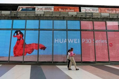 FILE PHOTO: Women walk past a Huawei P30 advertising LED board at a shopping centre in Bangkok