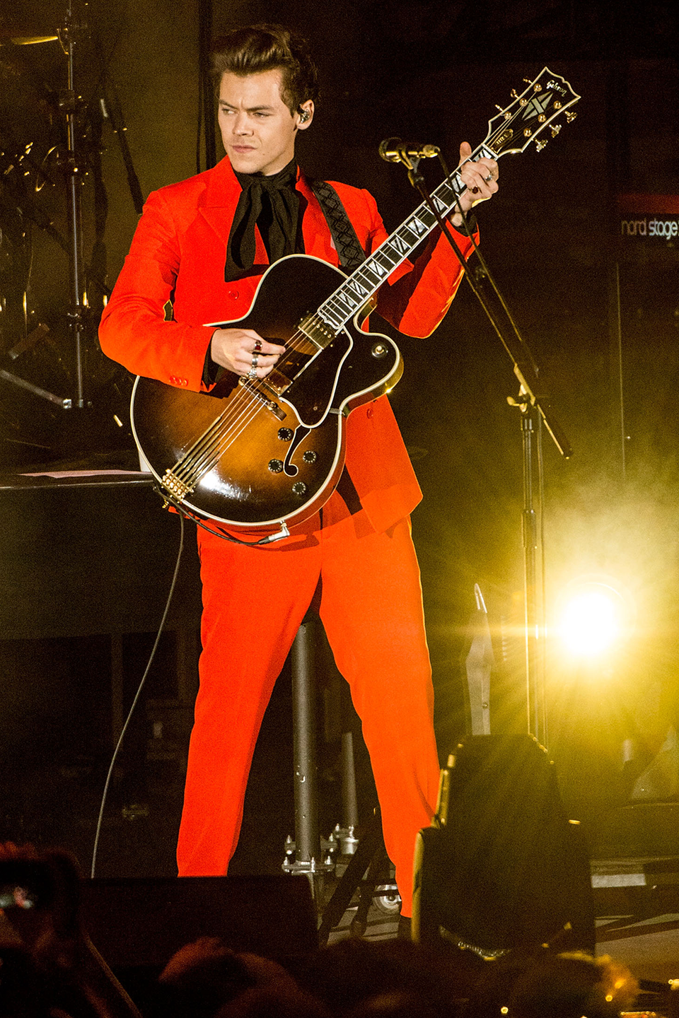 <p>Harry wore this bright red artwork while performing at a benefit concert in Hollywood. Oh look—he's shining so bright, my eyes have decided to tear up for me. :')</p>