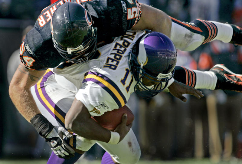FILE - In this Oct. 16, 2005 file photo, Minnesota Vikings quarterback Daunte Culpepper, bottom, is sacked for an 11-yard loss by Chicago Bears linebacker Brian Urlacher, top, during the fourth quarter in Chicago. Urlacher says he's retiring after spending 13 seasons with the Bears. The eight-time Pro Bowler announced his retirement through social media accounts Wednesday, May 22, 2013. (AP Photo/Jeff Roberson, File)