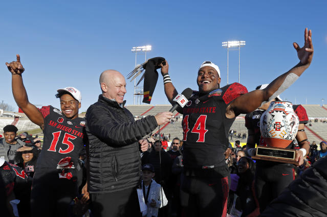 San Diego State linebacker Kyahva Tezino (44), recipient of the defensive MVP award, and running back Jordan Byrd (15), offensive MVP, celebrate after their team beat Central Michigan in the New Mexico Bowl NCAA college football game on Saturday, Dec. 21, 2019 in Albuquerque, N.M. (AP Photo/Andres Leighton)
