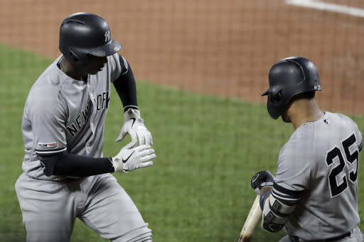 New York Yankees' Didi Gregorius, left, celebrates his solo home run off Baltimore Orioles starting pitcher Asher Wojciechowski with Gleyber Torres during the third inning of a baseball game Tuesday, Aug. 6, 2019, in Baltimore. (AP Photo/Julio Cortez)