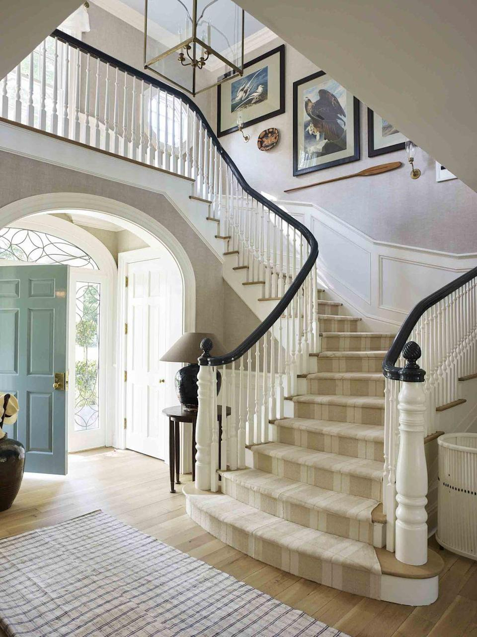 """<p>This serene stairwell offers a grand gesture and warm welcome to any one who steps inside the <a href=""""http://davidnettodesign.com/"""" rel=""""nofollow noopener"""" target=""""_blank"""" data-ylk=""""slk:David Netto"""" class=""""link rapid-noclick-resp"""">David Netto</a>-designed <a href=""""https://www.veranda.com/decorating-ideas/house-tours/a32721440/david-netto-connecticut-house/"""" rel=""""nofollow noopener"""" target=""""_blank"""" data-ylk=""""slk:1930s-style Colonial manse"""" class=""""link rapid-noclick-resp"""">1930s-style Colonial manse</a> in Connecticut. While Pablo Picasso earthenware and Audobon watercolors pepper the entryway, the home is well balanced with Friday night auction finds and trips to local purveyors in the Hudson Valley for a well-traveled yet well-rooted feel. The Wythe Blue-painted door (<a href=""""https://www.benjaminmoore.com/en-us"""" rel=""""nofollow noopener"""" target=""""_blank"""" data-ylk=""""slk:Benjamin Moore"""" class=""""link rapid-noclick-resp"""">Benjamin Moore</a>) and <a href=""""https://www.woodardweave.com/"""" rel=""""nofollow noopener"""" target=""""_blank"""" data-ylk=""""slk:Woodard Weave"""" class=""""link rapid-noclick-resp"""">Woodard Weave</a> carpet are eye-catching pops that still keep the room feeling full of restrained charm. </p>"""