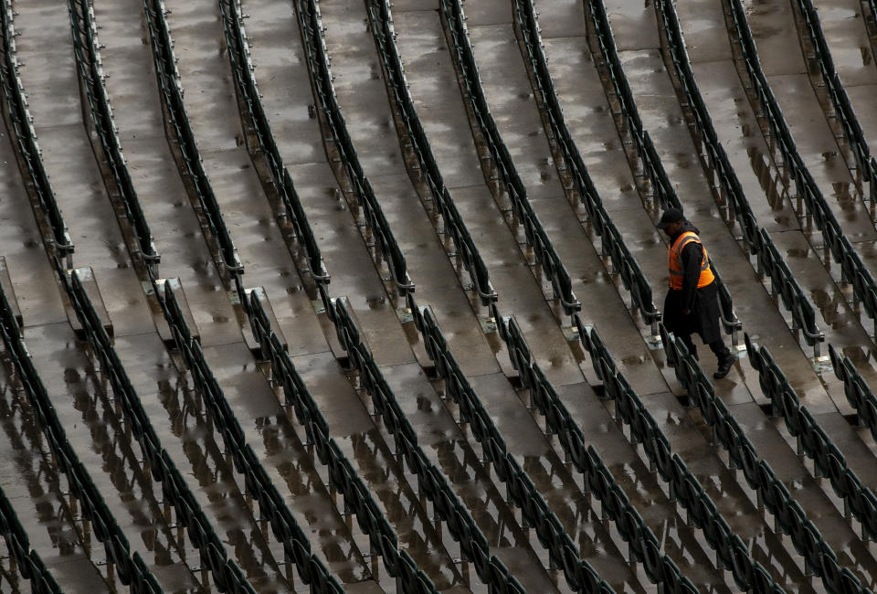 A man walks between empty chairs as rain has delayed the start of the fourth cricket test match between South Africa and England at the Wanderers stadium in Johannesburg, South Africa, Friday, Jan. 24, 2020. (AP Photo/Themba Hadebe)