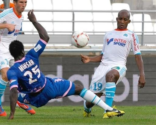 Marseille's Burkinabe midfielder Charles Kabore, right, challenges Evian's Ghanaian defender Jonathan Mensah for the ball during their League One soccer match at the Velodrome stadium, in Marseille, southern France, Sunday, Sept. 23, 2012. (AP Photo/Claude Paris)
