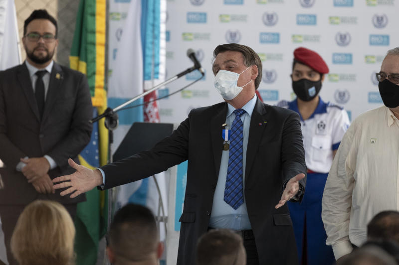 Brazil's President Jair Bolsonaro, wearing a mask due to the COVID-19 pandemic, greets people during the inauguration of the new civic-military school General Abreu in Rio de Janeiro, Brazil, Friday, Aug. 14, 2020. (AP Photo/Silvia Izquierdo)