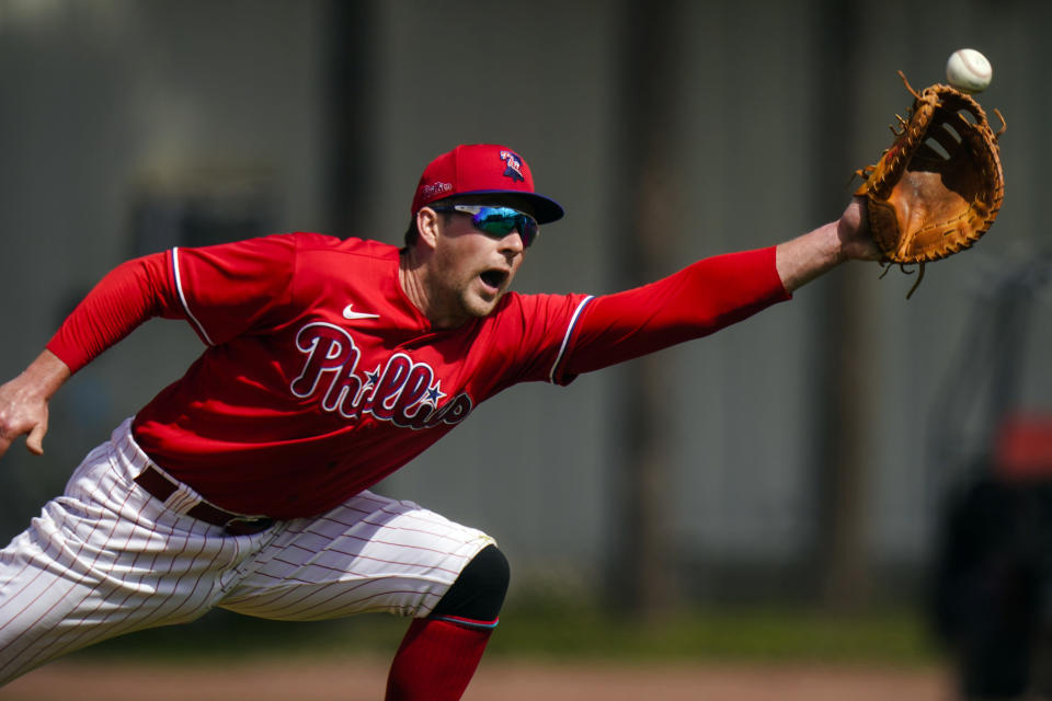 Philadelphia Phillies' Rhys Hoskins reaches for a ball during a spring training baseball workout Wednesday, Feb. 24, 2021, in Clearwater, Fla. (AP Photo/Frank Franklin II)