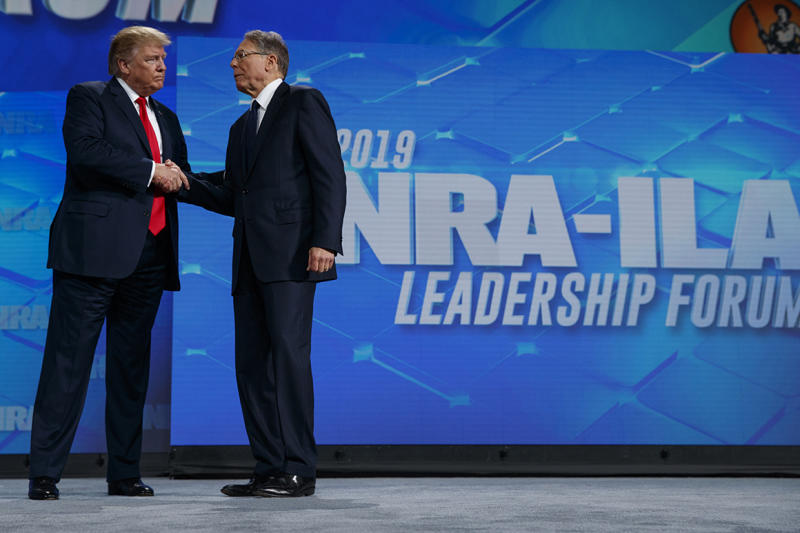President Donald Trump shakes hands with NRA executive vice president and CEO Wayne LaPierre as he arrives to speak to the annual meeting of the National Rifle Association, Friday, April 26, 2019, in Indianapolis. (AP Photo/Evan Vucci)