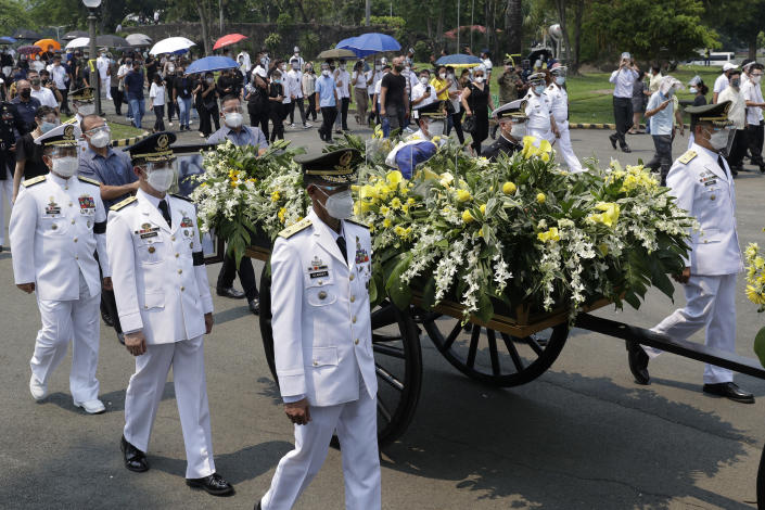 The urn of former Philippine President Benigno Aquino III is transported during state burial rites on Saturday, June 26, 2021 at a memorial park in suburban Paranaque city, Philippines. Aquino was buried in austere state rites during the pandemic Saturday with many remembering him for standing up to China over territorial disputes, striking a peace deal with Muslim guerrillas and defending democracy in a Southeast Asian nation where his parents helped topple a dictator. He was 61. (AP Photo/Aaron Favila)