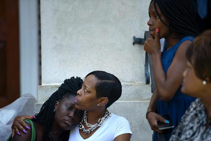 People sit on the steps of Morris Brown AME Church while services are held June 18, 2015 in Charleston, South Carolina (AFP Photo/Brendan Smialowski)