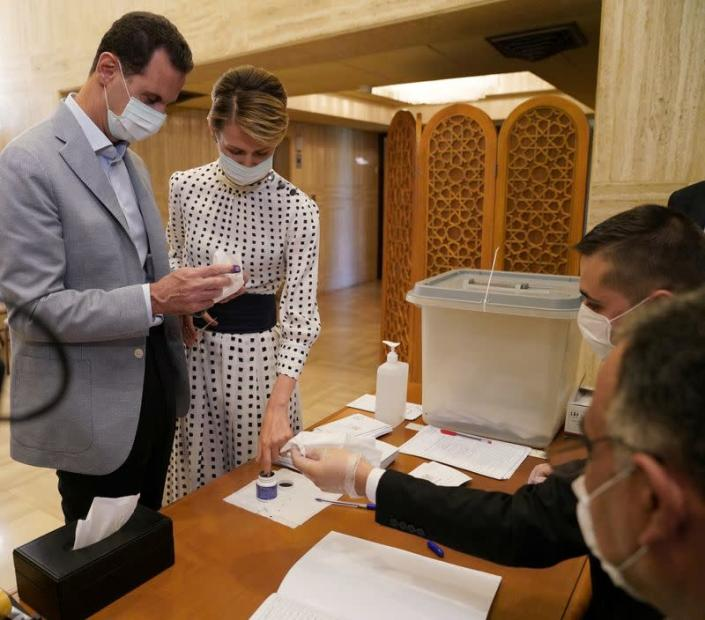 Syria's President Bashar al-Assad and his wife Asma cast their vote inside a polling station during the parliamentary elections in Damascus