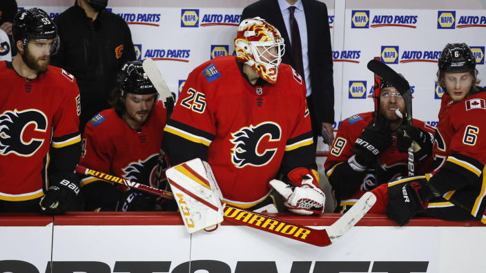 Calgary Flames goalie Jacob Markstrom, center, watches the play from the bench before a penalty is called against the Toronto Maple Leafs during second-period NHL hockey game action in Calgary, Alberta, Sunday, Jan. 24, 2021. (Jeff McIntosh/The Canadian Press via AP)