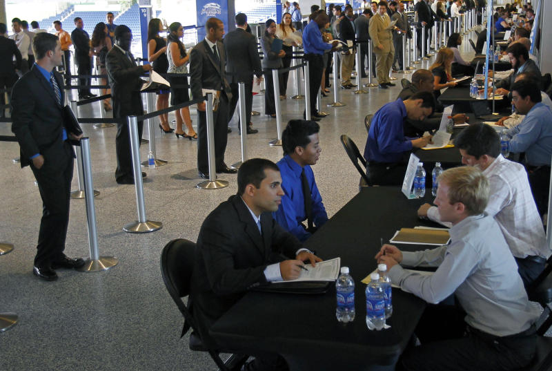 In this Wednesday, Oct. 24, 2012, photo, job applicants are interviewed by Florida Marlins staff at Marlins Park in Miami. Weekly applications for U.S. unemployment aid fell last week to a seasonally adjusted 369,000, a level consistent with modest hiring. The Labor Department said Thursday, Oct. 25, 2012, that unemployment benefit applications dropped by 23,000, from a revised 392,000 the previous week. (AP Photo/Alan Diaz)