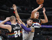 From left, Denver Nuggets forward Mason Plumlee, Charlotte Hornets center Willy Hernangomez and Nuggets forward Michael Porter Jr. look for a rebound ruing the first half of an NBA basketball game Wednesday, Jan. 15, 2020, in Denver. (AP Photo/David Zalubowski)