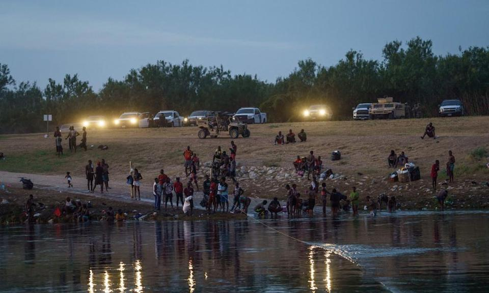 US border patrol, national guard and Texas department of public safety vehicles shine their lights on the Rio Grande migrant crossing point in Del Rio, Texas.